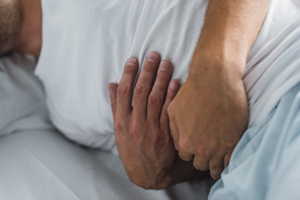 Man lying in bed holding his stomach