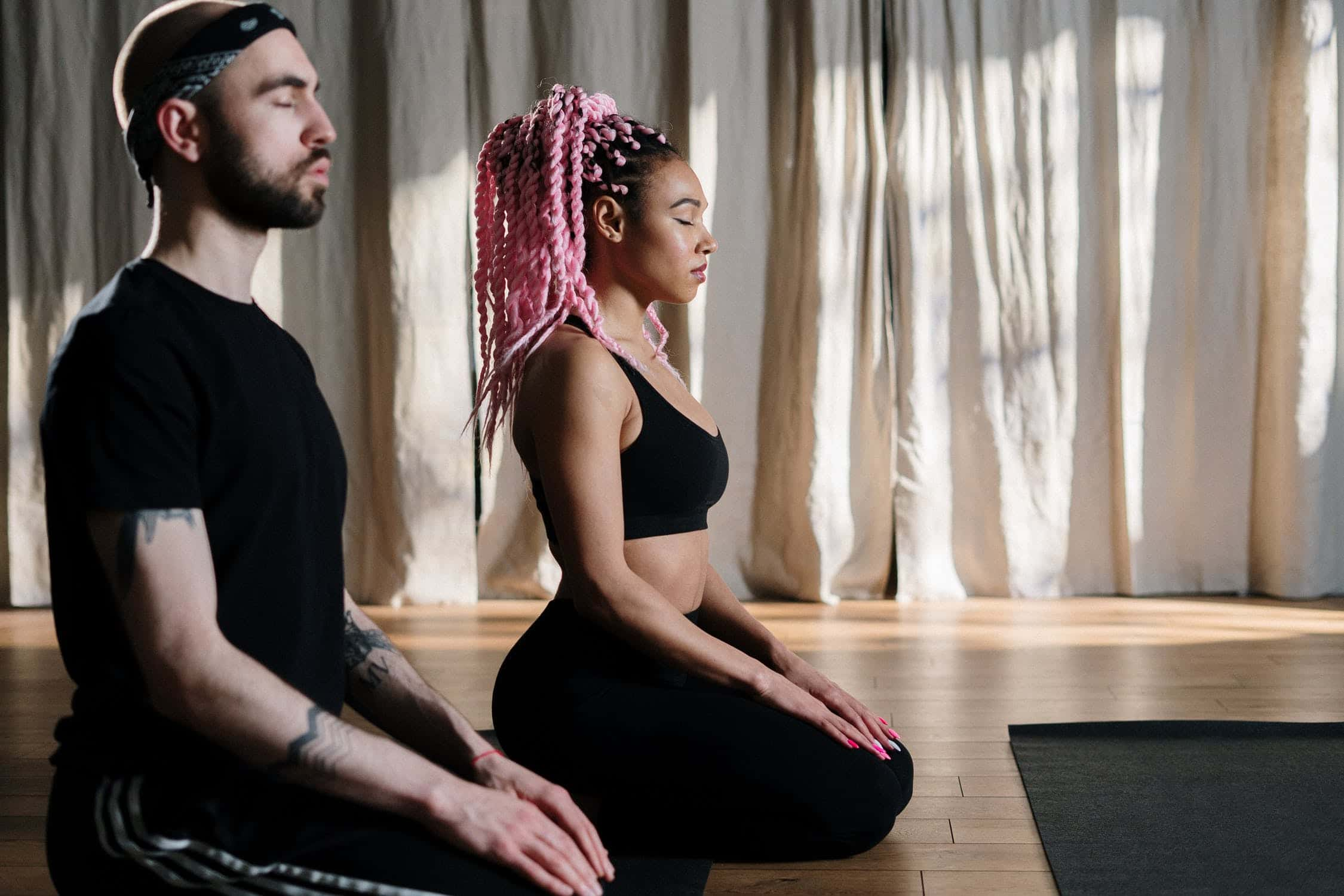 A man and a woman grounding before their yoga practice